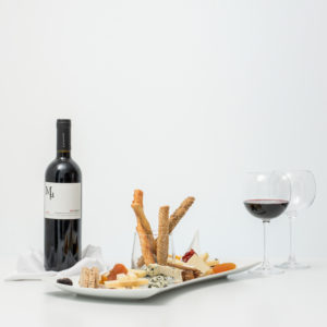 Bottle Of Red Wine With Cheese Platter And Dried Fruits